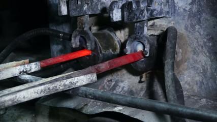 Выход  отлитого металлического стержня из плавильной печи.