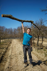 Powerful teenager raising a tree trunk in an orchard
