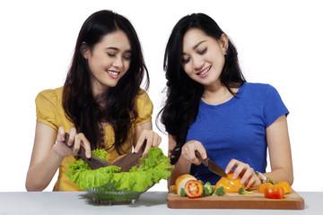 Cheerful girls cooking vegetables salad