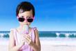 Child with sunglasses eats ice cream