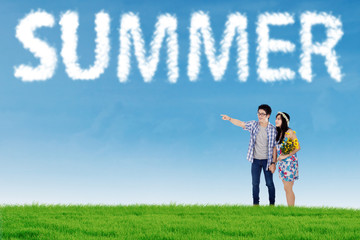 Couple look at cloud shaped summer text