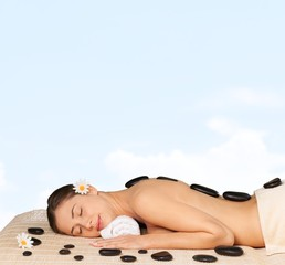 Spa Treatment. Spa salon: woman relaxing on mat with flowers and