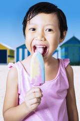 Happy little girl eating ice cream at coast