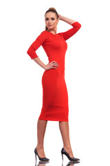 Attractive fashion woman wearing a slim red dress walking