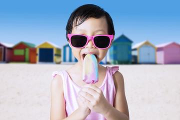 Kid eats cold ice cream at shore