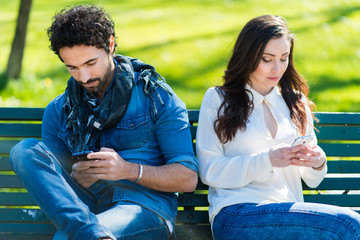 Couple not talking to each other typing on mobile phones