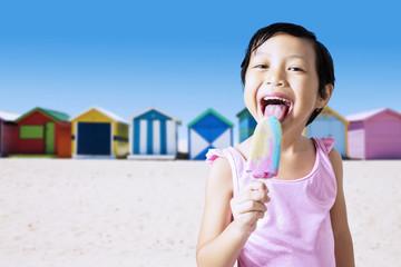 Lovely girl licking ice cream at beach