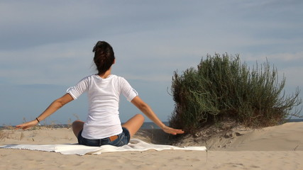 Young woman stretching and doing yoga on the beach