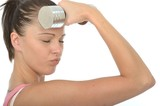 Healthy Young Woman Holding a Dumb Bell Weight to Her Forehead
