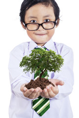 Smiling boy with plant in hands