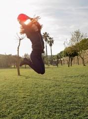 ragazza felice salta con pallone nel parco