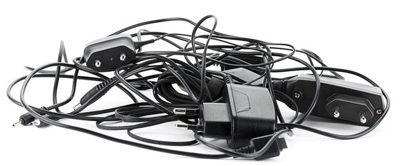 Heap of old cellular telephone chargers isolated