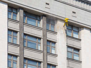 cleaner washes a large facade