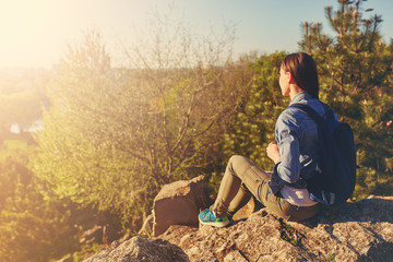 Young woman with backpack sitting on cliff