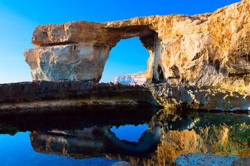 Azure Window, famous stone arch on Gozo island with reflection,