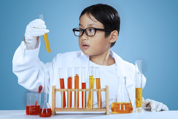 Young scientist looking at chemical fluid