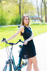 Young woman in short black dress with long hair rides a bicycle