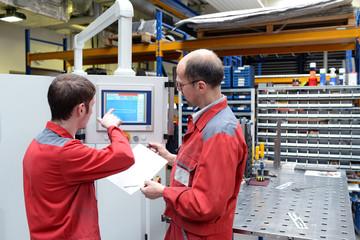 Berufsausbildung Handwerk, Meister und Azubi an CNC Maschine