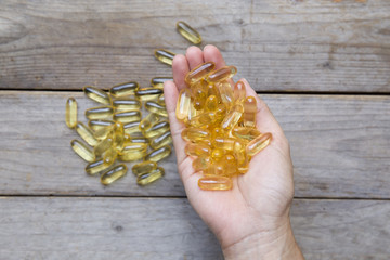 fish oil capsules in female hand on wood background