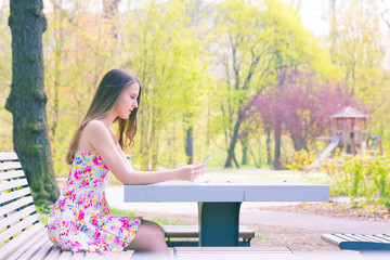 Young woman in short colorful dress sitting on a bench in summer