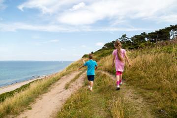 Kids walking along the coastline