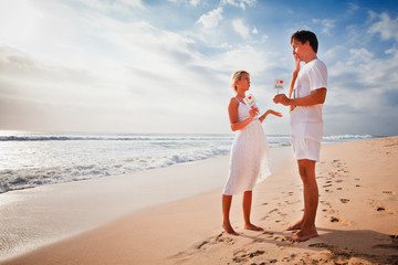 Beautiful couple on beach are holding frame with signs of love