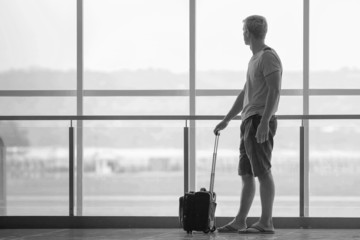 man with suitcase waiting a plane at terminal airport