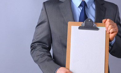 Young man standing with folder, isolated on gray background