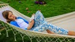 Girl reading a book in a hammock in the garden