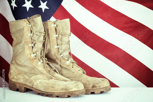 Leinwanddruck Bild Old combat boots with American flag
