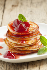 Hot pancakes with strawberry jam and mint leaves, selective focu