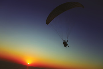 Paraglider silhouette against the background of the sunset sky