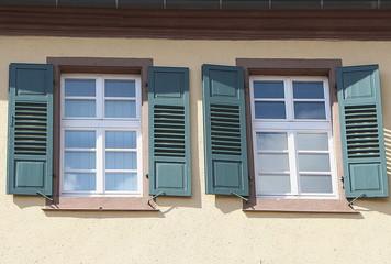 Zwei Fenster mit grünen Fensterläden