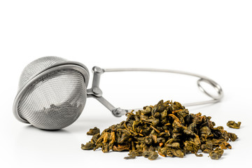 sieve and green tea leaves on a white background