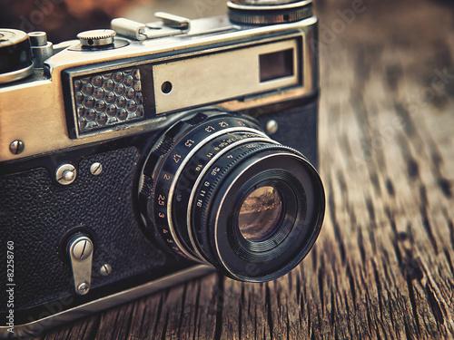Leinwanddruck Bild old vintage camera closeup on wooden background