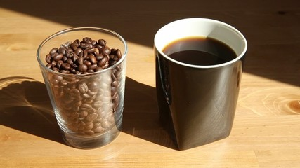 A hot steaming coffee cup with a glass full of coffee beans