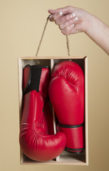 Pair of red boxing gloves in a wooden box