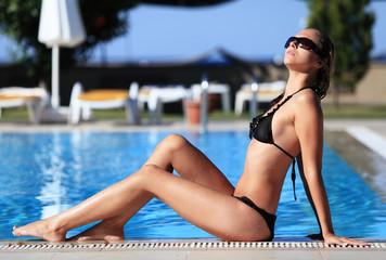 Woman sunbathing by swimming pool. Resort