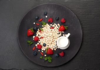 Oatmeal, milk and berries. Healthy breakfast. top view