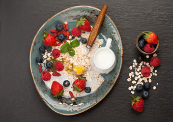 Oatmeal with milk, honey and berries. top view