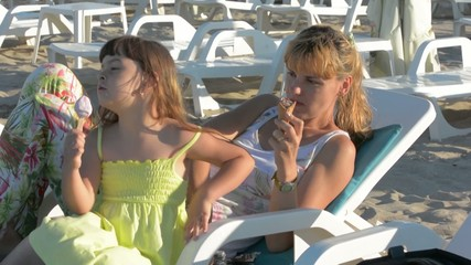 young mother with daughter eating ice cream sea