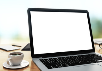 modern laptop on a table with blank white screen, shallow depth