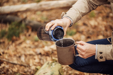 woman pours water from a bottle into a mug