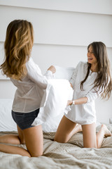 Two beautiful girls fighting with pillows