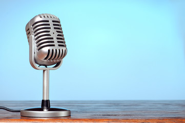Vintage microphone on the table with cyanic background