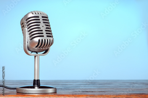 Leinwanddruck Bild Vintage microphone on the table with cyanic background
