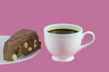 Coffee cup and milk chocolate isolated on pink
