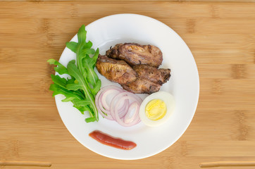 Roasted chicken liver with vegetable on wooden background