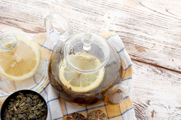 Ripe lemon, cinnamon and fruit drink in glass teapot on wooden
