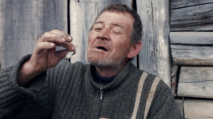 Poor old man smoking a homemade cigarette pathetic